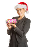 Woman weating Santa hat and holding a present.  Royalty Free Stock Photo