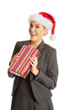 Woman weating Santa hat and holding a present.  Stock Images
