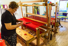 Woman weaver working at the loom and weaves red carpet. Woman weaver working at the loom and weaves the red carpet. The woman inserts the thread into the hook royalty free stock images