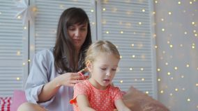 Woman weaves braids with little girl on a bed. Mother with with red manicure weaving braids with her daughter while sitting on the bed in slow motion stock footage