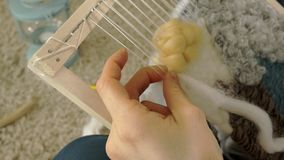 A woman weaves on a loom a beautiful embroidery made of yarn, in a home studio,. 4k stock video