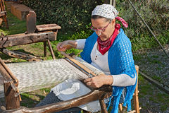 Woman weaves on old loom Stock Images