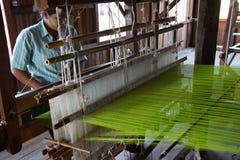 Woman weaving bright green silk Royalty Free Stock Image