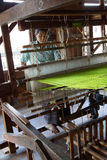 Woman weaving bright green silk Stock Images