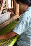 Woman weaving bright green silk Royalty Free Stock Photos