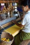 Woman weaving bright yellow silk Stock Photo