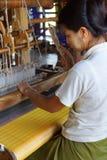 Woman weaving bright yellow silk Royalty Free Stock Image
