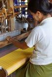 Woman weaving bright yellow silk Royalty Free Stock Photos