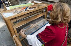 Woman weaving carpet Bulgaria. Woman, with traditional bulgarian clothes, weaving a carpet in Old town in Plovdiv, Bulgaria Royalty Free Stock Image