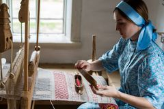 The woman is weaving the colorful cotton robe or dress by using wooden loom in the local village in Russia Royalty Free Stock Image