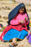 Woman weaving in the peruvian Andes at Puno Peru Stock Photo