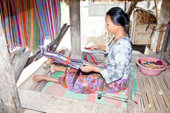 Woman is weaving , Sade village, Lombok. An elderly weave songket (traditional colorful fabric) using the classic loom in Sade,Lombok. Sade village is famous for stock photos