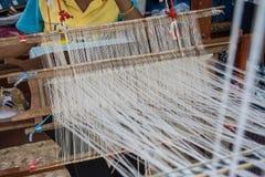 Woman weaving silk in traditional way at manual loom. Royalty Free Stock Photos