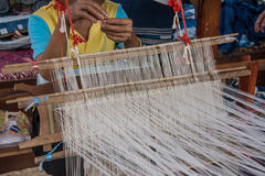 Woman weaving silk in traditional way at manual loom. Stock Photography
