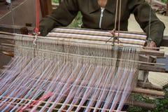 Woman weaving silk in traditional way at manual loom. Stock Photo