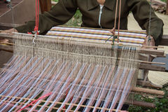 Woman weaving silk in traditional way at manual loom. Stock Photo