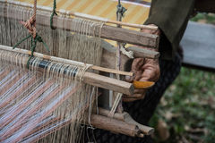 Woman weaving silk in traditional way at manual loom. Royalty Free Stock Photo