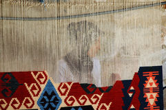 Woman weaving a traditional Turkish carpet, in Gor. GOREME, TURKEY - CIRCA JULY 2006: Woman weaving a traditional Turkish carpet, in Goreme, Turkey.  The carpets Stock Photos