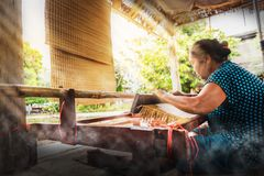 Woman weaving typical Thai straw mat from dry papyrus. Asian woman weaving typical Thai straw mat from dry papyrus royalty free stock images