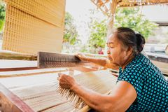 Woman weaving typical Thai straw mat from dry papyrus. Asian woman weaving typical Thai straw mat from dry papyrus royalty free stock photo