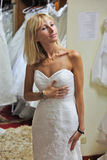 A woman in a wedding dress. A beautiful girl with hair bob is trying on a white wedding dress in one of the bridal salons. Beautiful figure, blonde girl is stock photography
