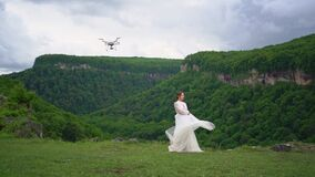 A woman in a wedding dress and black boots dances in the mountains.