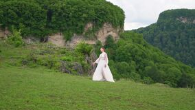 A woman in a wedding dress and black boots posing in the mountains.