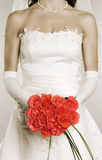 Woman in wedding dress with bunch of roses Royalty Free Stock Photography