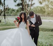 Woman in Wedding Dress Holding Flower With Man in Black Blazer stock photography