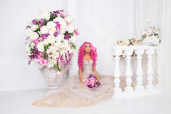 Woman in wedding dress posing. Model like a doll, in interior studio shooting, Royalty Free Stock Image