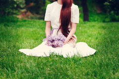 Woman in wedding dress sitting on the grass and holding a bouque Stock Images