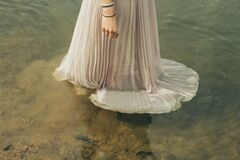 Woman in wedding dress standing in water