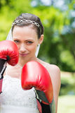 Woman in wedding dress wearing boxing gloves Stock Photo