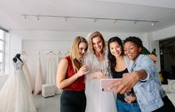 Bride with friends taking selfie in bridal boutique. Woman in wedding gown with female friends taking selfie in bridal boutique. Beautiful bride in elegant Royalty Free Stock Photography