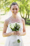 Woman in wedding gown holding bouquet in garden Stock Images