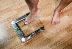 The woman weighed on the scales. Stock Images