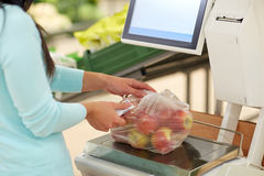 Woman weighing apples on scale at grocery store Royalty Free Stock Photography
