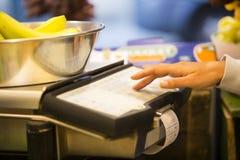 Woman weighing banana in supermarket Royalty Free Stock Image