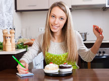 Woman weighing cakes on kitchen scales Royalty Free Stock Photography