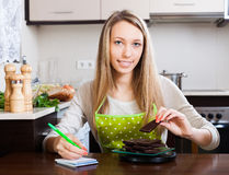 Woman weighing chocolate on kitchen scales Stock Photography
