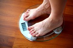 Woman weighing herself on the home scale Royalty Free Stock Images