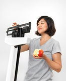 Woman Weighing Herself on Scale with Apple Royalty Free Stock Image