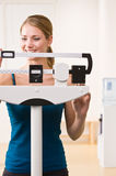 Woman weighing herself on scales in health club Royalty Free Stock Images