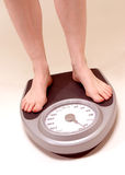 Woman on weighing machine Royalty Free Stock Image