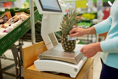 Woman weighing pineapple on scale at grocery store Stock Images