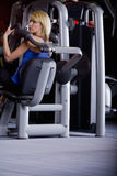 Woman weight lifting with exercise equipment in health club Royalty Free Stock Image