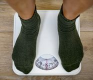 Woman on a weight scale stock image