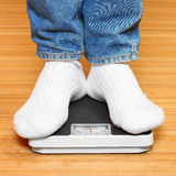 Woman on weight scale. Royalty Free Stock Image