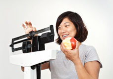 Woman on Weight Scale Pleased with Her Weight Loss. Happy woman weighing herself on medical weight scale, smiling and pleased with her weight loss Stock Images