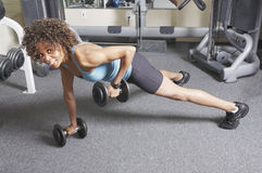 Woman weight training. African American woman doing floor exercises with free weights Royalty Free Stock Image